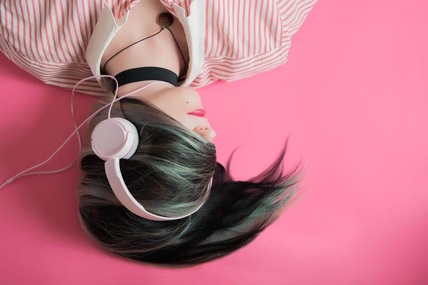 dziewczyna w słuchawkach na różowym tle